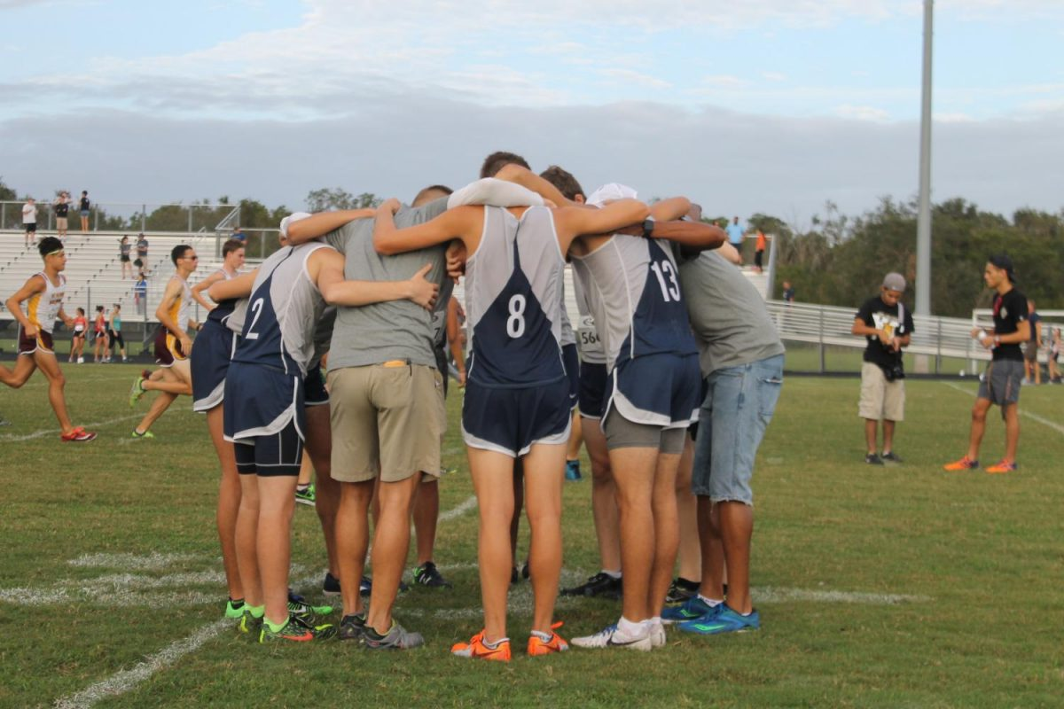 Boys Cross Country team huddled up before their race at the St. Cloud Invitational