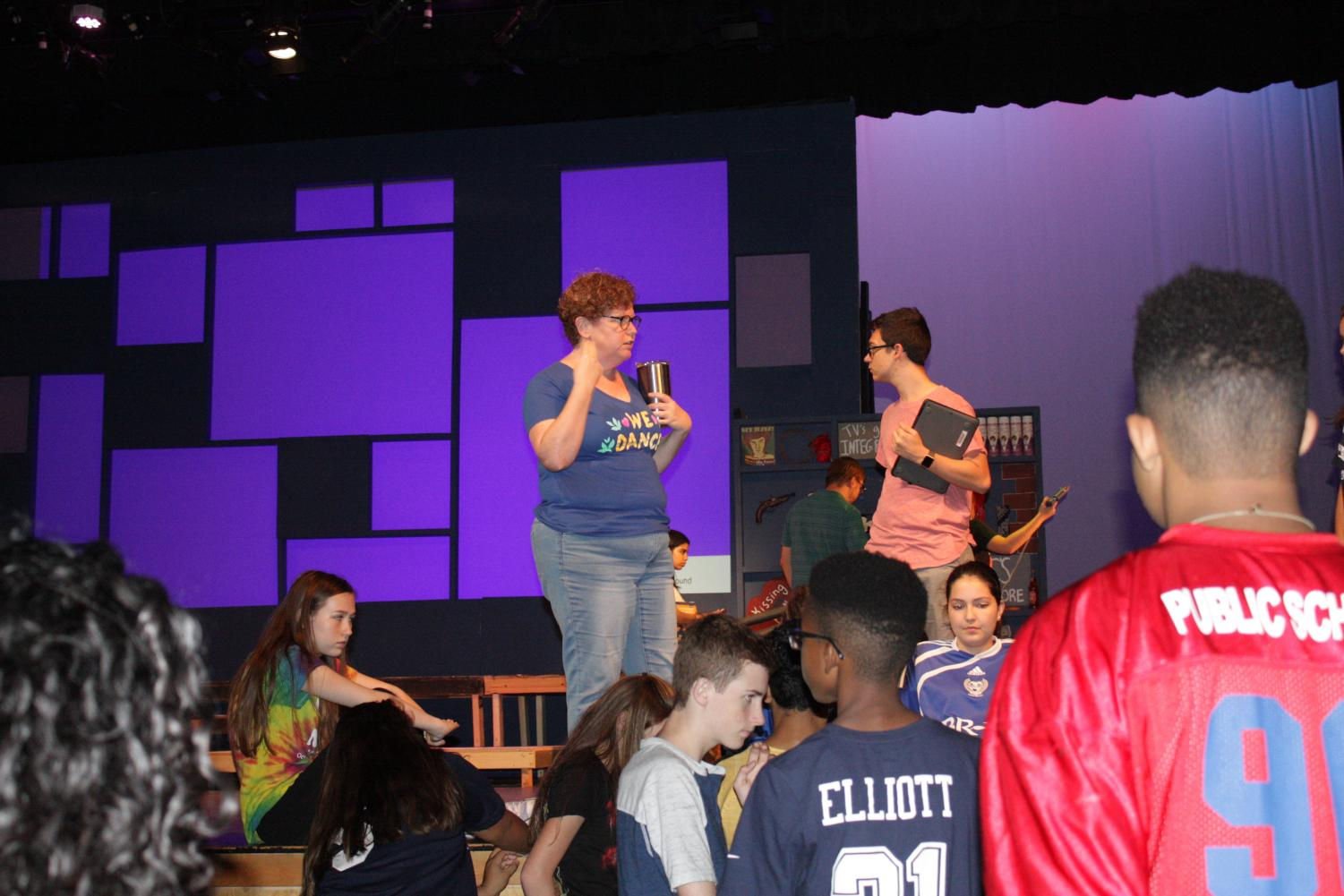 ( Mrs. Chase, Brenden Friedel 11, Sabrina Henson 10, Jackie Jara 12, Dante Fisher 10, Chijioke Oparaji 9) Mrs. Chase and Brenden Friedel speaking to the cast about what they need to improve on as a whole; In the auditorium on stage and off stage during rehearsals.