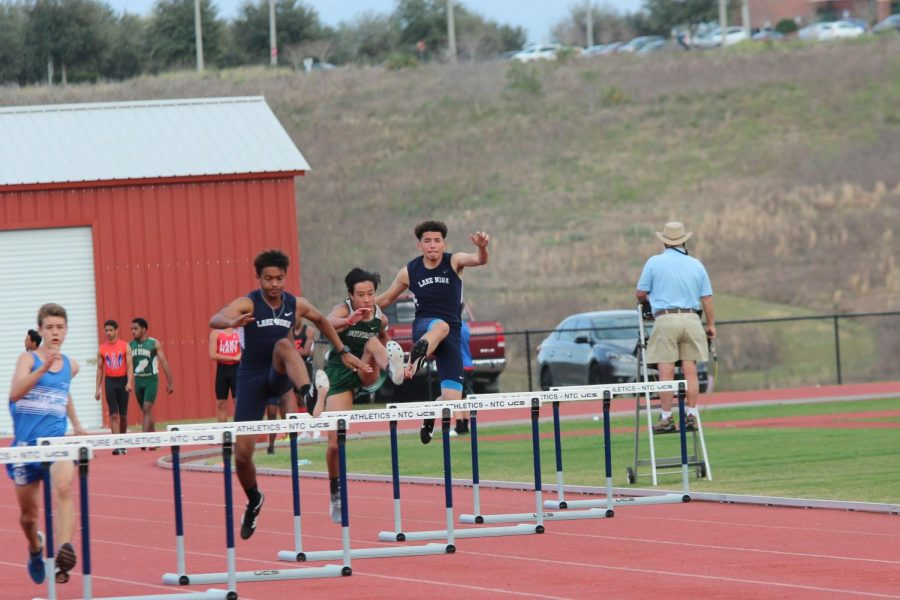 Rodney Vincent, 11, and Ethan Kassem, 10, leaping over hurdles in the 300M.