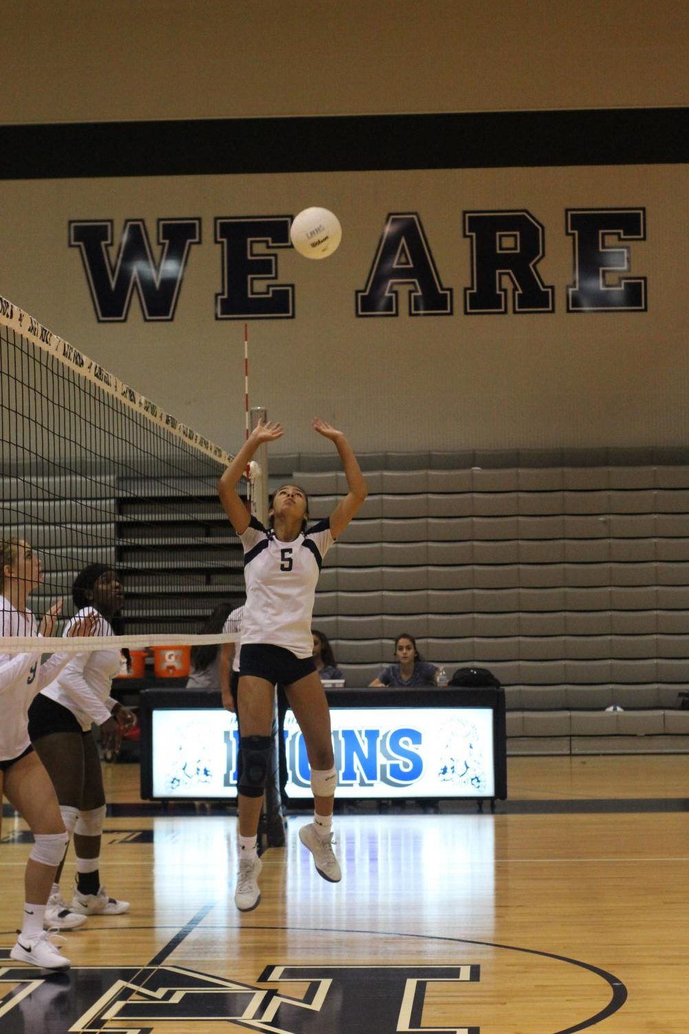 Racquel Misra (11) sets the ball for her teammate Zoe Glover (11) to spike and gain another point for the Lions.